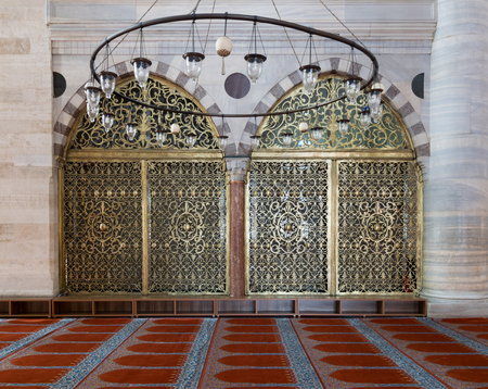 Interior shot of two arched ornate engraved golden doors, big chandelier over marble wall with pillars and red decorated carpet at Suleymaniye Mosque, Istanbul, Turkey Editorial