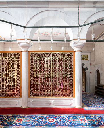 Golden ornate perforated partition framed in white marble arch and ornate carpet at Fatih Mosque, Istanbul, Turkey