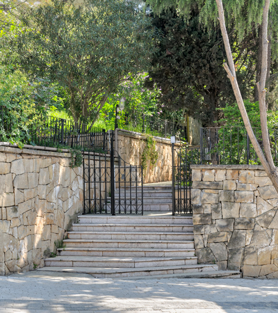 Ascending marble stairs leading to a public park, Stone wall, and fence iron door, Buyukada Island, Istanbul, Turkey