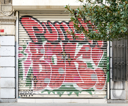 Istanbul, Turkey - April 18, 2017:  Closed shop exterior with metal door covered with colorful graffiti near Istiklal Street, Istanbul, Turkey