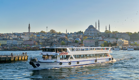 Istanbul, Turkey - April 25, 2017: City view of Istanbul, Turkey from the sea overlooking a passing ferry with Eminonu district and Sulaymaniye Mosque in the background Editorial
