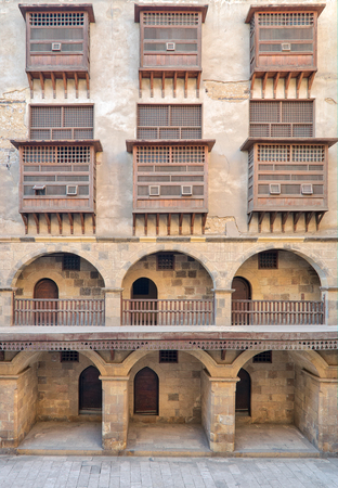 interleaved: Facade of caravansary (Wikala) of Bazaraa, with vaulted arcades and windows covered by interleaved wooden grids (mashrabiyya), suited in Tombakshia street, Al Gamalia district, Medieval Cairo, Egypt Stock Photo