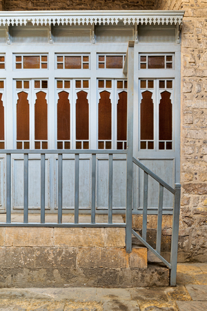 Array of wooden blue doors with yellow glass over stone wall, wooden blue balustrade, and stone stairs at historical traditional bathhouse (Hamam Inal), Cairo, Egypt