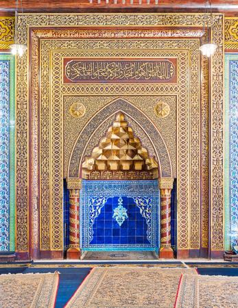 Golden ornate arched mihrab (niche) with floral pattern, blue Turkish ceramic tiles and arabic calligraphy at the public mosque of The Manial Palace of Prince Mohammed Ali Tewfik, Cairo, Egypt