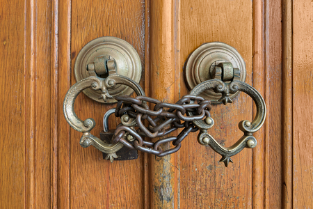 Closeup of two antique copper ornate door knockers over an aged wooden ornate door closed with rusted chain and padlock, Eyup Sultan Mosque, Istanbul, Turkey