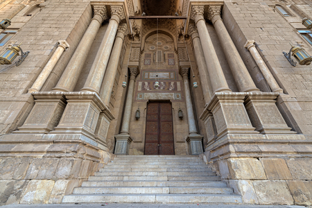 Entrance of al Rifai Mosque with closed decorated wooden doors, ornate columns, ornate recessed stone wall and stairs, Old Cairo, Egypt Stock Photo