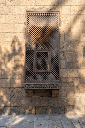 Ancient grunge wall with oriel window covered by interleaved wooden grid (Mashrabiya), Cairo, Egypt