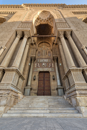 Entrance of al Rifai Mosque with closed decorated wooden door, ornate columns, ornate recessed stone wall and stairs, Old Cairo, Egypt Stock Photo