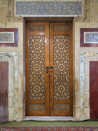 Old aged wooden closed door decorated with arabesque ornaments, Old Cairo, Egypt Stock Photo