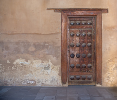 Grunge wooden aged door on grunge stone wall, Medieval Cairo, Egypt Stock Photo