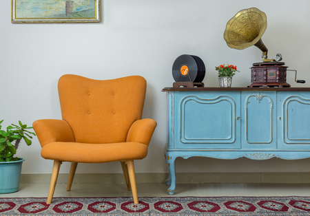 Vintage interior of retro orange armchair, vintage wooden light blue sideboard, old phonograph (gramophone), vinyl records on background of beige wall, tiled porcelain floor, and red carpet Archivio Fotografico