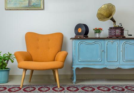 レトロなオレンジ色のアームチェア、ヴィンテージ木製ライトブルーのサイドボード、古い蓄音機(蓄音機)、ベージュの壁の背景にビニールレコード、タイル張りの磁器の床、およびレッドカーペットのヴィンテージインテリア