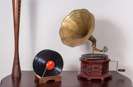 Still life of a nineteenth century phonograph (gramophone) and vinyl records on a wooden table and beige wall Stock Photo