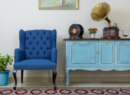 Vintage interior of retro blue armchair, vintage wooden light blue sideboard, old phonograph (gramophone), vinyl records on background of beige wall, tiled porcelain floor, and red carpet Фото со стока