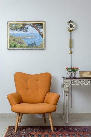 Vintage Furniture - Interior composition of retro orange armchair, vintage wooden beige table, and pendulum clock over off white wall, tiled beige floor and orange ornate carpet Stock Photo