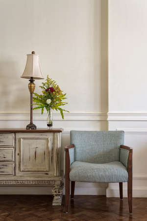 Interior shot of light blue armchair and cream vintage sidebar with table lamp and flowers planter on off white wall and wooden floor Stock Photo