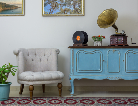 Vintage interior of retro off white armchair, vintage wooden light blue sideboard, old phonograph (gramophone) and vinyl records on background of beige wall, tiled porcelain floor, and red carpet Stock Photo