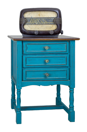 Vintage Furniture - Turquoise commode (Chest of Drawers) with 3 drawers with brass fittings and aged analog radio isolated on white background