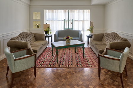 Interior shot of luxury modern living room with three couches, two armchairs, and vintage wooden table on background of big window with white curtains and decorated carpet on barquet floor
