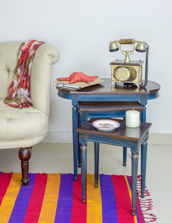 Interior shot of old golden telephone set, white candle, red starfish and colorful ornate plate over three nested tables with blue legs over off white wall, colorful Capet, and cream armchair Stock Photo