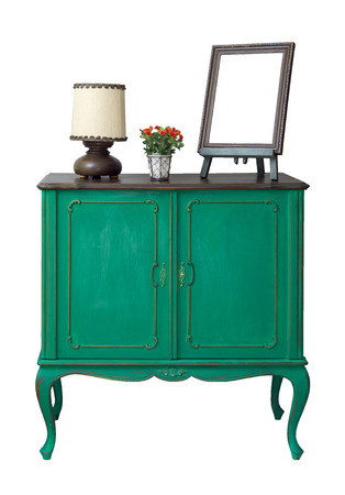 Wooden green vintage sideboard with empty wooden ornate brown desktop photo frame, flower planter, and table lamp isolated on white including clipping path