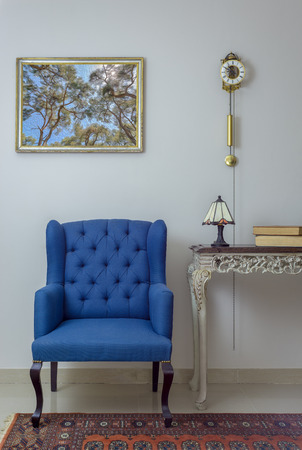 Vintage Furniture - Interior composition of retro blue armchair, vintage wooden beige table, table lamp, books, and pendulum clock over off white wall, tiled beige floor and orange ornate carpet Stock Photo