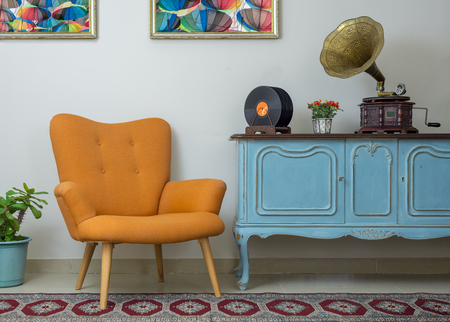 Vintage interior of retro orange armchair, vintage wooden light blue sideboard, old phonograph (gramophone), vinyl records on background of beige wall, tiled porcelain floor, and red carpet Stock Photo