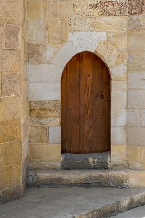 Grunge wooden aged vaulted door on exterior stone bricks wall of Amir Aqsunqur Mosque (Blue Mosque), Medieval Cairo, Egypt
