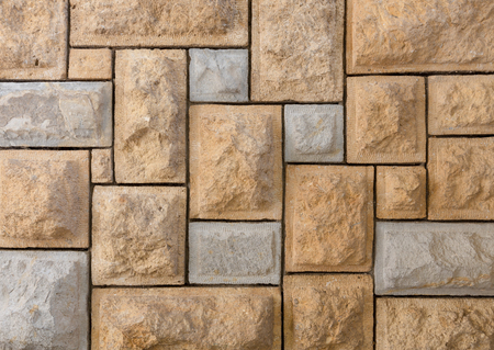 Background of pattern of yellow and gray decorative uneven stone wall surface