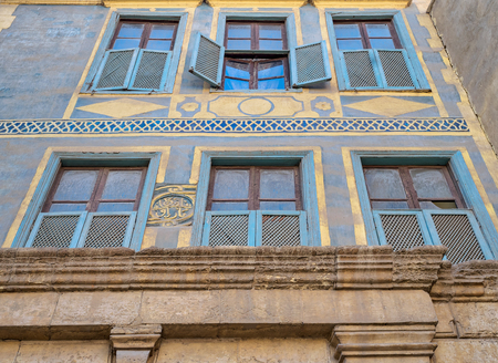 Facade of Beit (house) El Harrawi with glass windows, wooden grids and ornate wall painted in yellow and blue, an old Mamluk era eighteenths century historic house in Medieval Cairo, Egypt Stock Photo