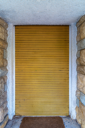 Background of bricks stone wall and closed yellow roll-up door Stock Photo