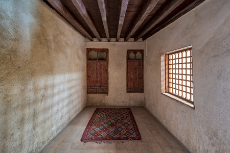 Room at El Sehemy house, a historic old Ottoman era house located in Cairo, built in 1648, with embedded wooden cupboard, wooden window and colorful carpet, Cairo, Egypt Stock Photo