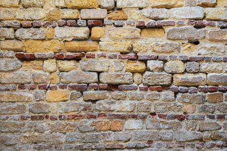 Background of irregular pattern of yellowish, red and gray grunge weathered uneven bricks stone wall surface Stock Photo