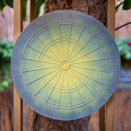 Dartboard game board painted in green, yellow and blue hanged on tree with blurred background of public garden
