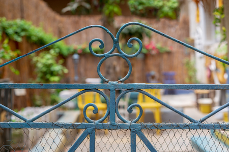 Vintage artistic green wrought iron gate with peeling paint and rust revealing blurred garden in the background Stock Photo