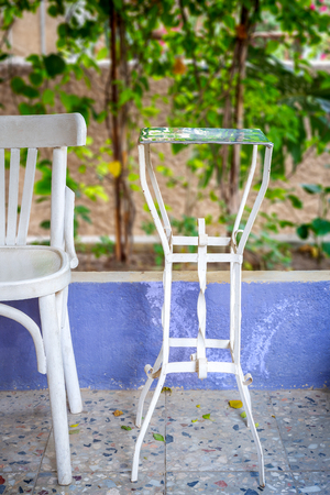 Traditional Egyptian metal tea table and white wooden chair on blurred background of green climber plant Stock Photo