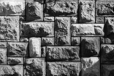 Black white shot of background of pattern of decorative uneven stone wall surface