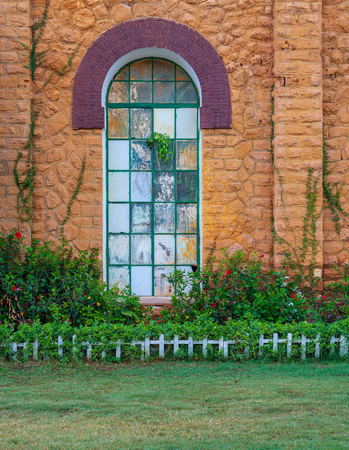 Orange colored bricks stone wall with big old grunge window covered with green metal grid, green grass floor, and plants at summer time, Montazah Public park, Alexandria, Egypt