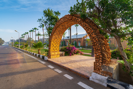 Stone bricks orange arch leading to the royal plant nursery with trees and palms in sunrise time at Montazah public park, Alexandria, Egypt