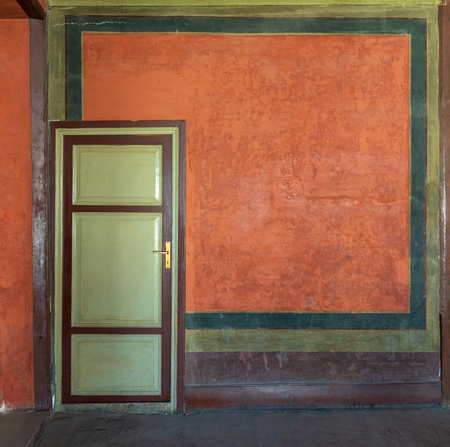 Colorful painted wall and green wooden door at the historic building of Mevlevi Tekke, Cairo, Egypt Stock Photo