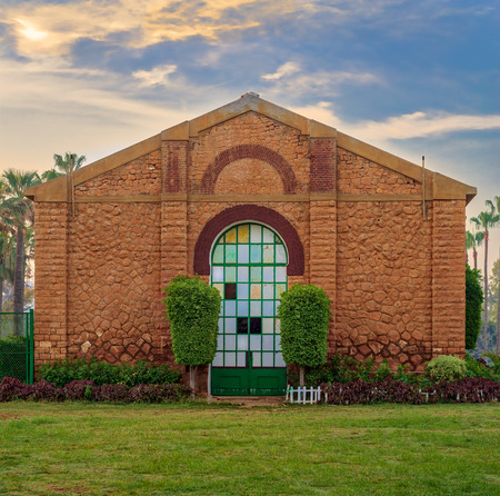 Side view of the Royal Plant Nursery with closed grunge door and orange painted bricks stone wall decorated with plants in sunrise time at Montaza public park, Alexandria, Egypt Stock Photo