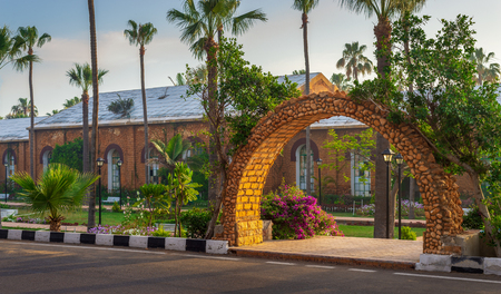 Stone bricks orange arch revealing the royal plant nursery at Montazah public park with trees and palms in sunrise time, Alexandria, Egypt