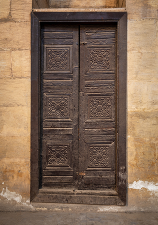 Wooden aged grunge door and stone bricks wall, Medieval Cairo, Egypt