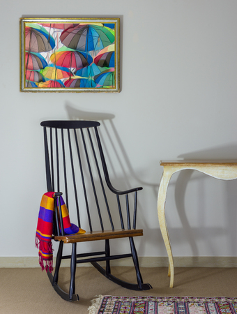 Classic rocking chair and off white vintage table on background of off white wall with hanged painting