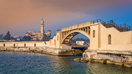 Bridge in the mediterranean sea at the tea island of Montazah park and the Royal palace in the far distance with calm sea at sunrise time, Alexandria, Egypt Stock Photo