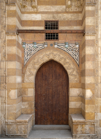 Wooden aged grunge door and stone bricks wall, one of the exterior doors of Aqsunqur Mosque (Blue Mosque) located in Bab El-Wazir District, Medieval Cairo, Egypt