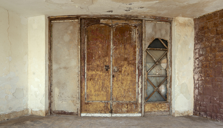 Abandoned old grunge weathered wooden double leaves door and brown stone bricks wall