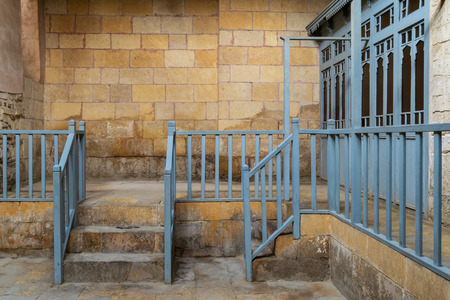 Abandoned historic traditional bathhouse (Hamam Inal) with staircase leading to bricks stone wall, wooden blue balustrade, and doors of changing rooms, Medieval Cairo, Egypt