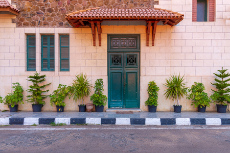 Facade of the clock tower in Montaza public park with green wooden door with red tile canopy above and window shutters on stone bricks wall, Alexandria, Egypt Stock Photo