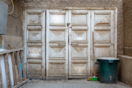 Wooden grunge weathered abandoned door painted in white, green trash can and ladder Stock Photo